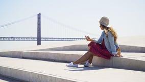 Mujer con el teléfono en orilla del mar almacen de metraje de vídeo