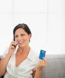 Mujer con el teléfono móvil de la tarjeta de crédito y de discurso Foto de archivo libre de regalías