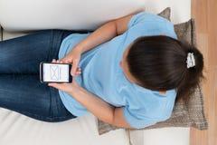 Mujer con el teléfono móvil que muestra el nuevo mensaje Imagen de archivo libre de regalías