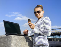 Mujer con el teléfono móvil y la computadora portátil Fotos de archivo libres de regalías