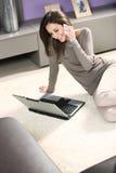 Mujer con el teléfono móvil y la computadora portátil Foto de archivo libre de regalías
