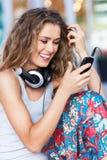 Mujer con el teléfono móvil y los auriculares Foto de archivo libre de regalías