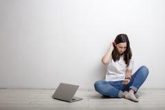Mujer con el teléfono móvil y los auriculares que se sientan cerca de una pared blanca Fotos de archivo libres de regalías