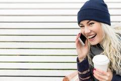 Mujer con el teléfono y el café a disposición que ríe Foto de archivo