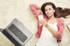 Mujer con el teléfono y el ordenador portátil, chica joven que usa el ordenador imágenes de archivo libres de regalías