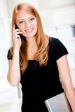 Mujer con el teléfono y la computadora portátil foto de archivo libre de regalías