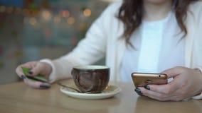 Mujer con el teléfono y tarjeta de crédito en una tabla en un café metrajes