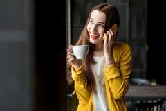 Mujer con el teléfono y una taza de café Fotos de archivo