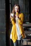 Mujer con el teléfono y una taza de café Imagenes de archivo