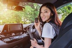 Mujer con el telecontrol dominante elegante en un coche foto de archivo libre de regalías