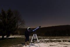 Mujer con el telescopio debajo de la mujer del cielo nocturno del invierno que mira a través del telescopio bajo noche estrellada Imagen de archivo libre de regalías