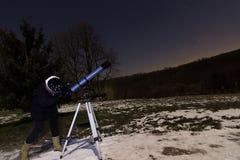 Mujer con el telescopio debajo de la mujer del cielo nocturno del invierno que mira a través del telescopio bajo noche estrellada Imagen de archivo
