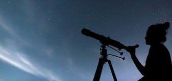 Mujer con el telescopio que mira las estrellas Mujer de la astronomía y ni fotografía de archivo