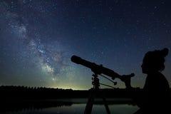 Mujer con el telescopio que mira las estrellas Mujer de la astronomía y ni imagen de archivo