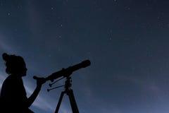 Mujer con el telescopio que mira las estrellas Mujer de la astronomía y ni foto de archivo libre de regalías
