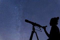 Mujer con el telescopio que mira las estrellas Mujer de la astronomía y ni foto de archivo
