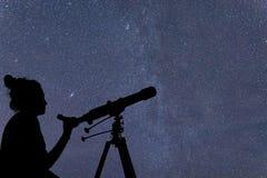 Mujer con el telescopio que mira las estrellas Mujer de la astronomía y ni imágenes de archivo libres de regalías