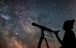 Mujer con el telescopio que mira las estrellas Mujer de la astronomía y ni imagenes de archivo