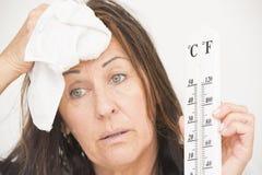 Mujer con el thermometre y el sudor foto de archivo