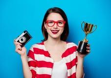 Mujer con el trofeo de la taza y la cámara retra Foto de archivo libre de regalías