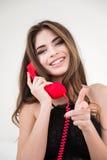Mujer con el tubo rojo del teléfono que señala el finger en la cámara Imágenes de archivo libres de regalías