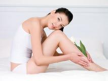 Mujer con el tulipán blanco en piernas perfectas Foto de archivo libre de regalías