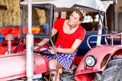 Mujer con el vestido del Dirndl que conduce el tractor Foto de archivo libre de regalías