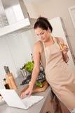 Mujer con el vidrio de vino blanco en la cocina Imagen de archivo libre de regalías