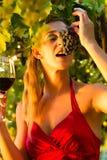 Mujer con el vidrio de vino que come las uvas Imagen de archivo libre de regalías