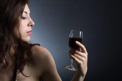Mujer con el vino rojo de cristal Foto de archivo libre de regalías