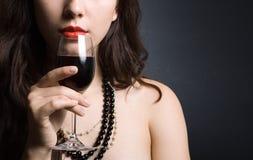Mujer con el vino rojo de cristal Fotos de archivo libres de regalías