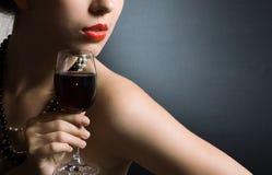Mujer con el vino rojo de cristal Imagen de archivo libre de regalías