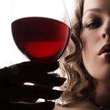 Mujer con el vino rojo de cristal Fotos de archivo