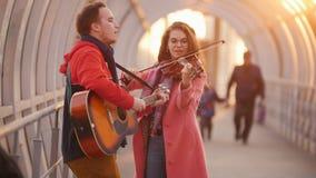 Mujer con el viol?n y el hombre con la guitarra que juega m?sica en el paso almacen de metraje de vídeo