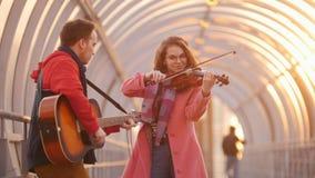 Mujer con el viol?n y el hombre con la guitarra que juega m?sica en el paso en la puesta del sol almacen de metraje de vídeo