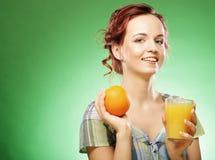 Mujer con el zumo de naranja sobre fondo verde Fotos de archivo libres de regalías