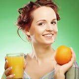 Mujer con el zumo de naranja sobre fondo verde Imágenes de archivo libres de regalías