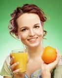 Mujer con el zumo de naranja sobre fondo verde Imagenes de archivo