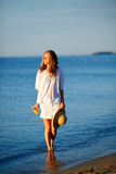 Mujer con el zumo de naranja y el sombrero de paja a disposición en la playa en la salida del sol Imágenes de archivo libres de regalías