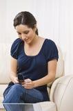 Mujer con envío de mensajes de texto del teléfono celular Imagenes de archivo