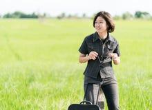 Mujer con equipaje que hace autostop a lo largo de un camino Fotografía de archivo libre de regalías