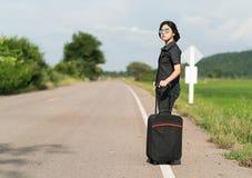 Mujer con equipaje que hace autostop a lo largo de un camino Fotografía de archivo