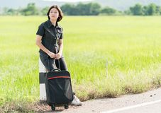 Mujer con equipaje que hace autostop a lo largo de un camino Foto de archivo