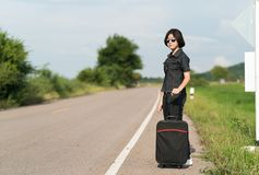 Mujer con equipaje que hace autostop a lo largo de un camino Imágenes de archivo libres de regalías