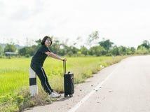 Mujer con equipaje que hace autostop a lo largo de un camino Imagenes de archivo