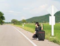 Mujer con equipaje que hace autostop a lo largo de un camino Imagen de archivo libre de regalías