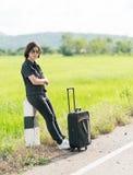 Mujer con equipaje que hace autostop a lo largo de un camino Fotos de archivo