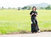 Mujer con equipaje que hace autostop a lo largo de un camino Imagen de archivo