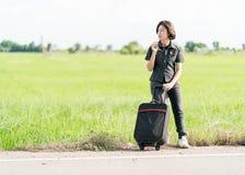 Mujer con equipaje que hace autostop a lo largo de un camino Foto de archivo libre de regalías