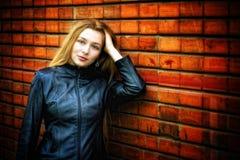 Mujer con estilo atractiva en la pared cercana de cuero imágenes de archivo libres de regalías